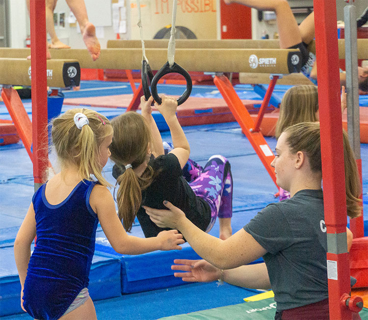 girls help another on the rings